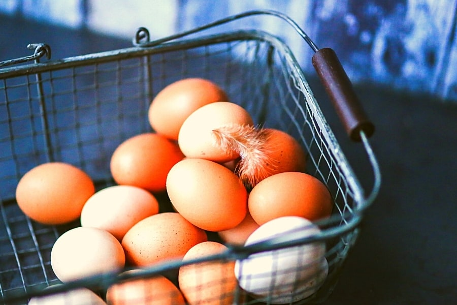 Brown eggs in wire basket with a feather to consider the risks in a monthly dividend strategy