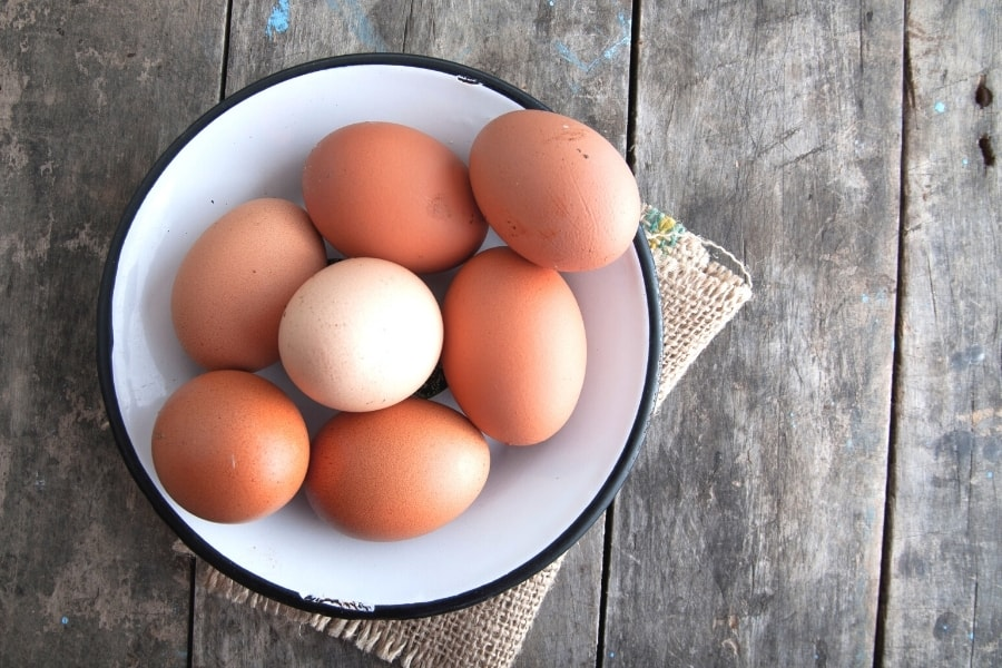 Brown eggs in white bowl to remember the risks in a monthly dividend strategy